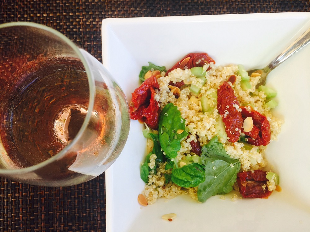 quinoa salad with tomatoes and basil with glass of rose wine from above - in my suitcase